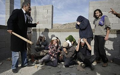 In this file photo taken Tuesday, Jan. 7, 2014, injured Israeli settlers are detained by Palestinian villagers in a building under construction near the West Bank village of Qusra, southeast of Nablus [AP/Nasser Ishtayeh]
