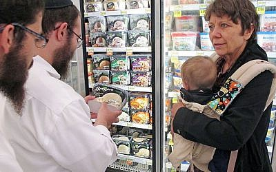 In this July 27, 2015 photo, Orthodox Jewish rabbi Dovid Lepkivker, center, examines a container of Breyer's ice cream, which happens to be kosher, as fellow rabbi Eli Chaikin, left, and Mary Semple look on in Helena, Mont.  (AP/Matt Volz)