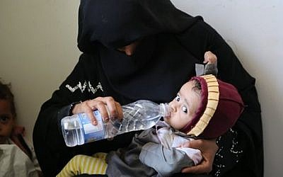 In this picture taken Tuesday, Aug. 18, 2015, a mother gives water to her child in Sanaa, Yemen, during a visit by Ertharin Cousin, Executive Director of the World Food Program. The United Nations says the war in Yemen has pushed the country to the brink of famine. (WFP/Abeer Etefa via AP)