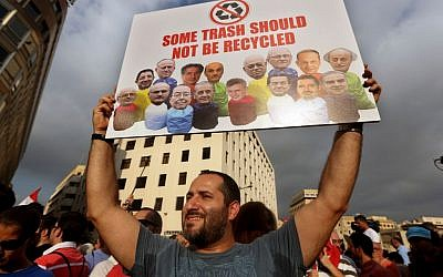 In this August 22, file photo, a Lebanese activist holds a poster with pictures of Lebanese Cabinet ministers during a protest against the ongoing trash crisis, in downtown Beirut, Lebanon. (AP Photo/Bilal Hussein, File)
