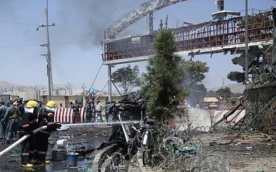 Afghan fire fighters extinguish vehicles on fire after an attack at the main gate of International Hamed Karzai Airport in Kabul, Afghanistan, Monday, Aug. 10, 2015. (Massoud Hossaini/AP)