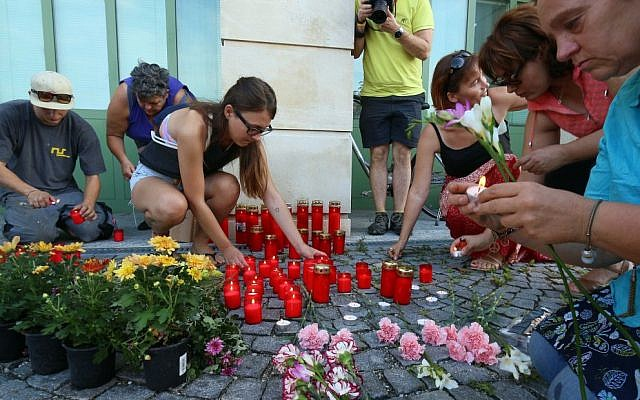 People light candles in front of the police station in Eisenstadt, Austria, Thursday, Aug 27, 2015. Austrian police on Thursday discovered the badly decomposing bodies of 71 migrants stacked in a truck parked on the shoulder of the main highway from Budapest to Vienna near Eisenstadt. (AP Photo/Ronald Zak)