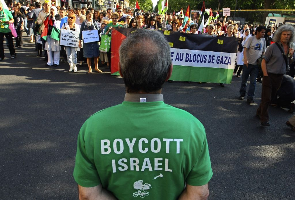 Protesters shout slogans during a rally in Paris, France, Thursday, June 3, 2010, as they demonstrate against Israel's raid on a Gaza-bound aid ship, and man in foreground wears a t-shirt calling for a boycott on Israel. (Jacques Brinon/ AP)