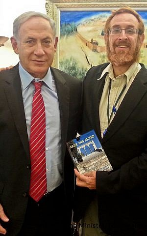 Temple Mount activist and would-be Likud MK Yehuda Glick hands Prime Minister Benjamin Netanyahu a copy of the guidebook 'Arise and Ascend' on August 19, 2015 (courtesy Yehuda Glick)