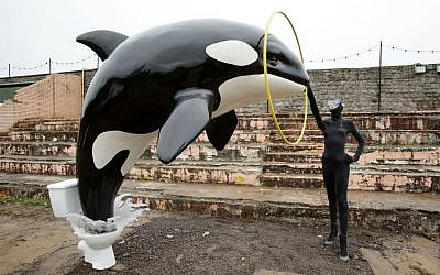 A Banksy piece depicting an orca whale jumping out of a toilet is displayed at Banksy's biggest show to date, entitled 'Dismaland', during a press viewing in Western-super-Mare, Somerset, England, Thursday, August 20, 2015. (Yui Mok/PA Wire via AP)