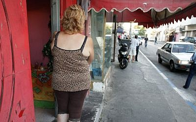 Illustrative photo of a prostitute outside a brothel in south Tel Aviv, looking at a police woman nearby, September 21, 2008. (Kobi Gideon / FLASH90)