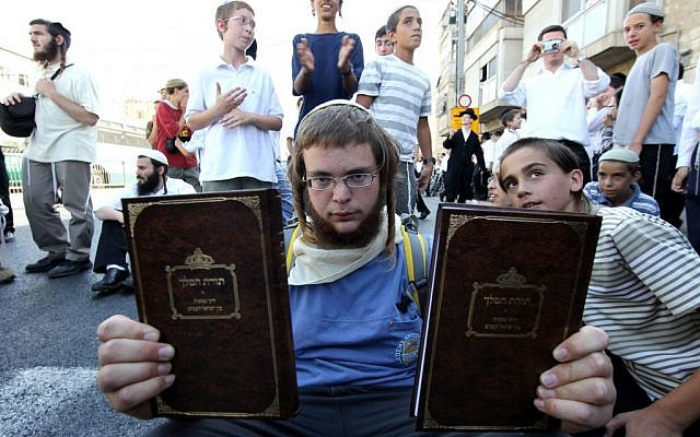 An Orthodox young man holds up copies of the book Torat Hamelech in which it is stated that the killing of non-Jews is permitted in certain situations, July 3, 2011 Nati Shohat/Flash90