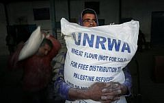 Palestinians receive their monthly food aid at a United Nations distribution center in the Rafah refugee camp, in southern Gaza Strip, February 8, 2015 (Abed Rahim Khatib/Flash90)