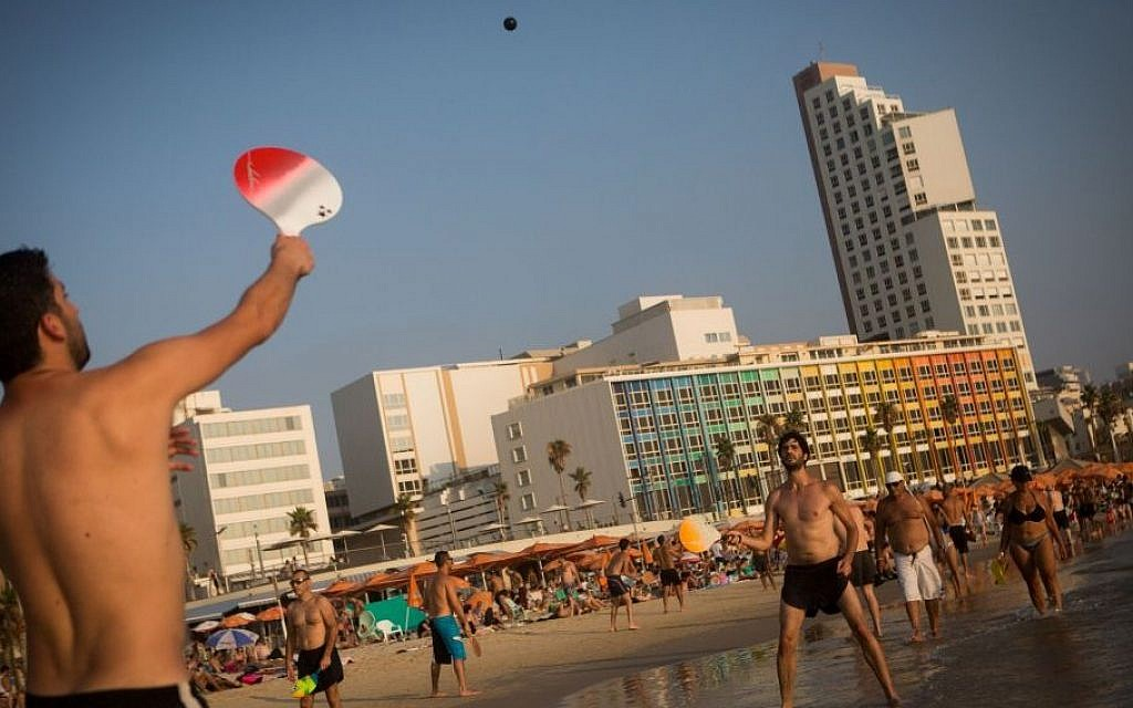 People play beach tennis (matkot), on the beach in Tel Aviv on a hot summer day, August 1, 2015. (Miriam Alster/Flash90)