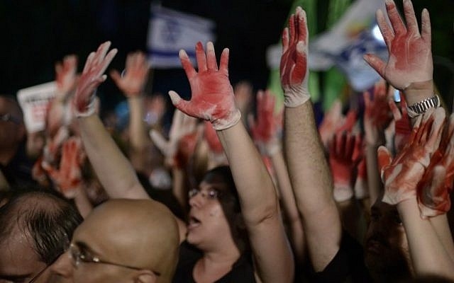 Demonstrators hold up hands painted in red to signify blood while protesting an address by Likud minister Yuval Steinitz at an anti-violence and anti-homophobia rally in Tel Aviv, on August 01, 2015. (Tomer Neuberg/Flash90)