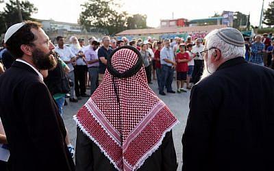 Sheikh Ibrahim Ahmad Abu el-Hawa (center), with Rabbi Yaakov Nagen (left) and Rabbi Benjamin Kalmanzon, both from the Otniel Yeshiva, along with other rabbis, during a prayer vigil for the Dawabsha family at the Gush Etzion Junction, August 2, 2015. (Nati Shohat/Flash90)