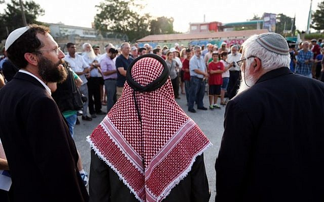 Sheikh Ibrahim Ahmad Abu el-Hawa (center), with Rabbi Yaakov Nagen (left) and Rabbi Benjamin Kalmanzon, both from the Otniel Yeshiva, along with other rabbis, during a prayer vigil for the Dawabsha family at the Gush Etzion Junction, August 2, 2015. (Nati Shohat/Flash90)