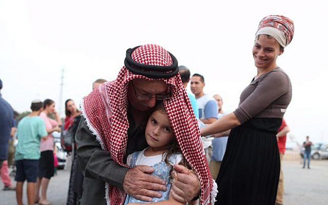 Sheikh Ibrahim Ahmad Abu El-Hawa embraces an Israeli girl at a prayer vigil at the Etzion Junction for the Dawabsha family on Sunday. (Nati Shohat/Flash90)
