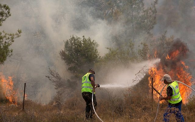 Illustrative: Israel Nature and Parks Authority workers try to extinguish a brush fire near Moshav Even Sapir, just outside of Jerusalem, on August 2, 2015. (Yonatan Sindel/Flash90)