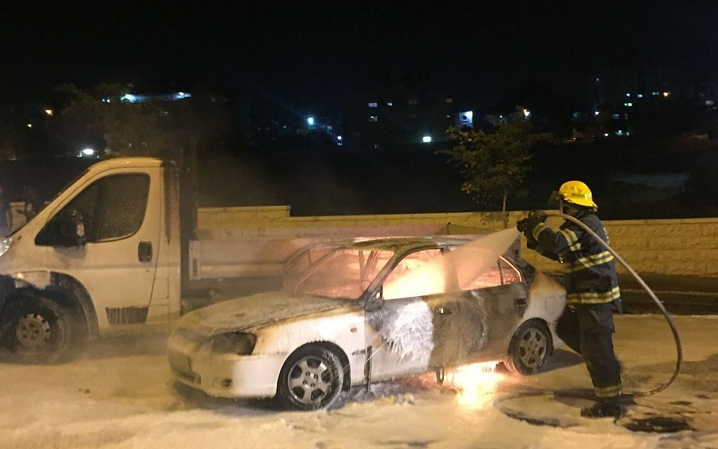 Firefighters extinguish a car that caught fire after it was hit by a Molotov cocktail near the Arab neighborhood of Beit Hanina in East Jerusalem, injuring three people, on Monday night, August 3, 2015 (Sliman Khader/FLASH90)