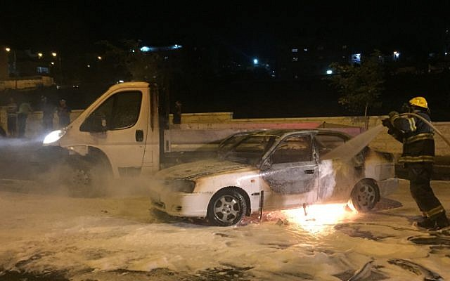 Firefighters extinguish a blazing car after it was hit by a Molotov cocktail near the Arab neighborhood of Beit Hanina in East Jerusalem, August 3, 2015. (Sliman Khader/Flash90)