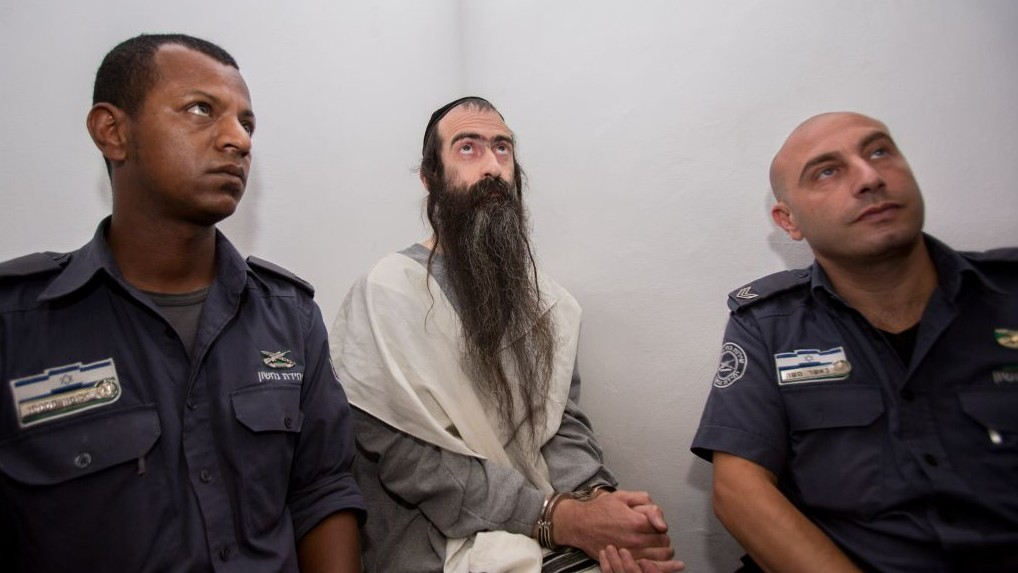 Yishai Schlissel, center, an ultra-Orthodox Jew who stabbed a teenage girl to death at the Jerusalem Gay Pride Parade, is seen at the Jerusalem Magistrates Court on August 5, 2015. (Yonatan Sindel/Flash90)