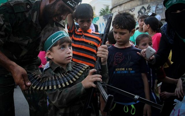 A Palestinian boy holds his father's weapon during a graduation ceremony as part of a military-style summer camp organised by the  Izzadin al-Qassam brigades, the armed wing of the Hamas movement, on August 5, 2015, in Khan Yunis. (Abed Rahim Khatib/ Flash90)