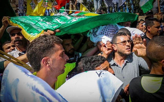Palestinian men carry the body of Saad Dawabsha, the father of a Palestinian toddler killed last week when their home was firebombed by perpetrators suspected to be Jewish extremists, during his funeral in the West Bank village of Duma on August 08, 2015. (FLASH90)