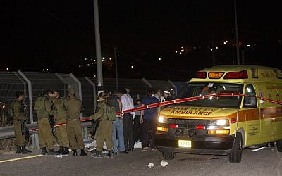 Israeli security forces stand by the body of a Palestinian man who was shot after stabbing an Israeli on Sunday night, August 9, 2015, at a gas station on the 443 road to Jerusalem (Yonatan Sindel/Flash90)