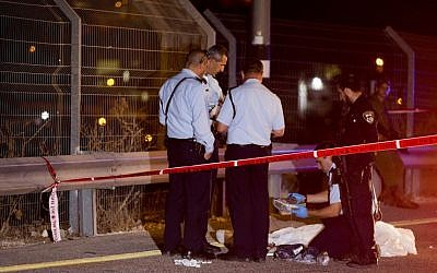 Israeli security forces stand by the body of the terrorist who stabbed an Israeli at the Route 443 gas station, near Jerusalem, August 9, 2015. (Yonatan Sindel/Flash90)