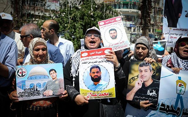Protesters hold portraits of Palestinian prisoner Mohammad Allan, who is held in Israeli jail, during a protest in the West Bank city of Ramallah, August 11, 2015 Flash90