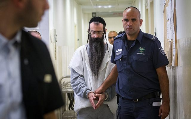 Accused Jerusalem Gay Pride Parade attacker Yishai Schlissel is escorted by police after his hearing at the Jerusalem District Court on August 11, 2015. (Miriam Alster/Flash90)