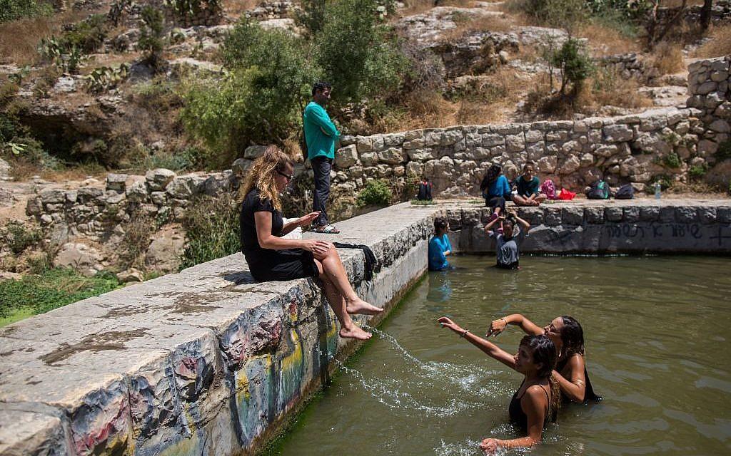 Israelis cooling off at Lifta spring outside Jerusalem on August 16, 2015. (Yonatan Sindel / Flash90)