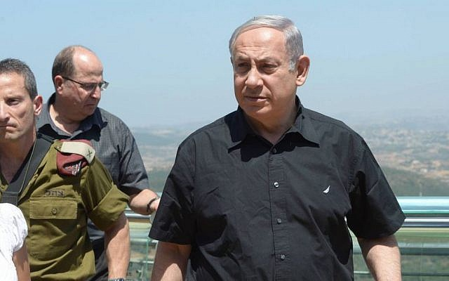 Israeli Prime Minister Benjamin Netanyahu seen during his visit to the northern border of Israel on August 18, 2015. Defense Minister Yaalon is behind him. (Amos Ben Gershom/GPO)