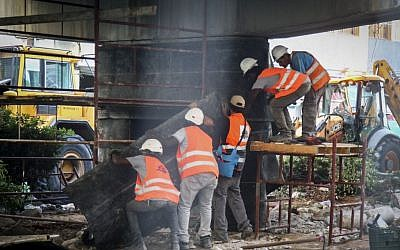 A crew works on Tel Aviv's partly destroyed Maariv bridge -- which was completely demolished on August 21 -- on August 19, 2015. (Flash90)