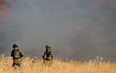 IDF soldiers stand near a large brush fire outside Kfar Sold in the Golan Heights sparked by four missiles fired from the Syrian side of the Israeli-Syrian border on August 20, 2015. (Basel Awidat/Flash90)
