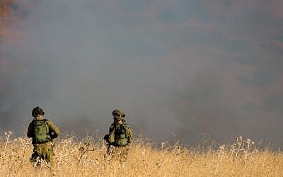 Two IDF soldiers stand amid a large fire raging near Kfar Sold, caused by missiles fired from the Syrian side of the Israeli-Syrian border and hitting open areas in the Golan Heights in northern Israel on August 20, 2015. (Basel Awidat/Flash90)