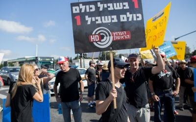 Israel Broadcast Authority employees holds signs as they protest against planned dismissals in Jerusalem on August 30, 2015 (Yonatan Sindel/Flash90)