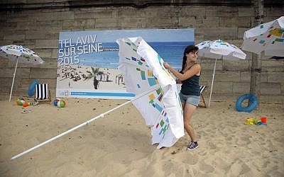 A volunteer installs a sun umbrella on the sand as part of the Paris Tel Aviv Beach on the banks of the Seine Rive in Paris, France, Thursday, Aug. 13, 2015 (AP Photo/Francois Mori)