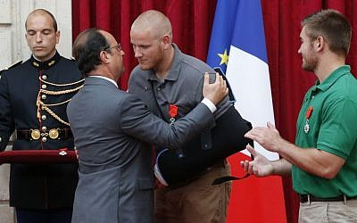 French President Francois Hollande, second left, hugs US Airman Spencer Stone, center, while US National Guardsman Alek Skarlatos applauds after they were awarded with the Legion of Honor at the Elysee Palace, Paris, France, August 24, 2015. (AP/Michel Euler, Pool)