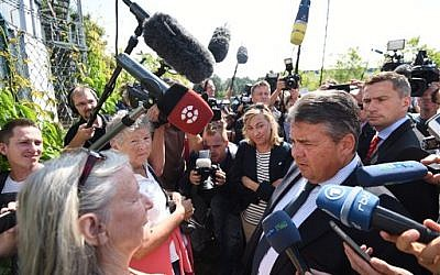 File: Germany's vice-chancellor Sigmar Gabriel talks to journalists as he visits a refugee shelter that was attacked by far-right protesters over the weekend in Heidenau, eastern Germany, Monday Aug. 24, 2015. (Rainer Jensen/dpa via AP)