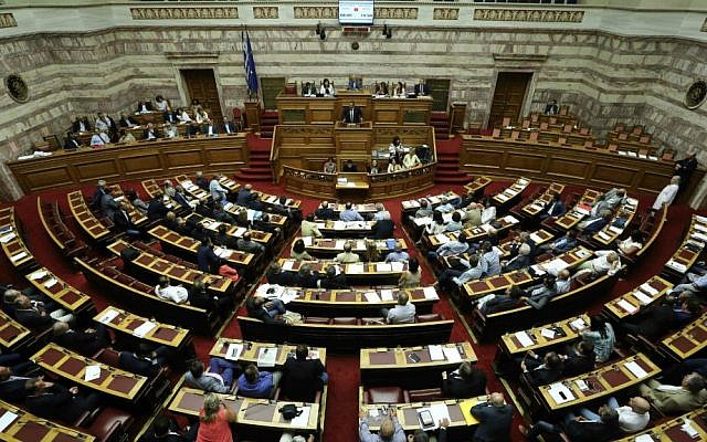 Greek lawmakers take part in a parliamentary session in Athens, Friday, Aug. 14, 2015, a debate in parliament to approve a massive new bailout deal with European creditors and governments. (AP Photo/Yannis Liakos)