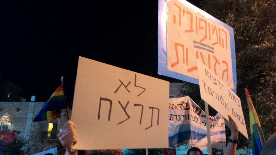 "Demonstrators hold signs at a rally against incitement and hatred in Jerusalem on Saturday August 1 2015. The signs read ""Thou shalt not Kill,"" ""Homophobia = Racism"" and ""How Many will be Killed in the Name of God?"" (Yoav Shamash)"
