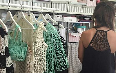 Dani Peleg, at her home studio with a selection of her 3D printed clothing (Zahava Presser/Times of Israel)