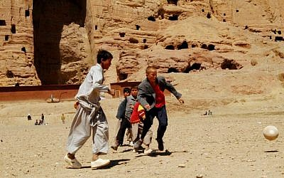 In this Monday, April 9, 2007, file photo, Afghan boys play soccer in front of the area where the enormous Buddha statues once stood in Bamiyan province, before their destruction at the hands of the Taliban in March 2000. (AP Photo/Amir Shah, File)