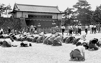 In this Aug. 15, 1945 photo, Japanese people kneel in front of the Imperial Palace in Tokyo as Emperor Hirohito announced on radio that Japan was defeated in the World War II.  (Kyodo New via AP)