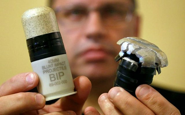 In this Thursday, July 30, 2015 photo, Salvatore Emma Jr., president and CEO of Micron Products, displays Blunt Impact Projectiles, one ready for use, left, and another after being fired during a test at the factory in Fitchburg, Massachusetts. (AP Photo/Steven Senne)