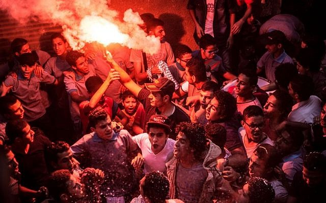 In this Tuesday, June 23, 2015, members of Ultras Nahdawy, a youth group of the Muslim Brotherhood, sing anti-army chants in a protest ahead of the second anniversary of the ouster of Islamist President Mohammed Morsi in the Nahia district, near Cairo, Egypt. (AP Photo/Belal Darder)