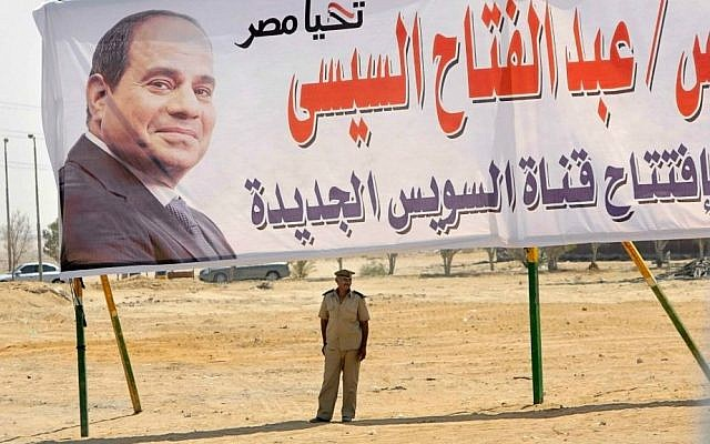 A policeman stands alert under a billboard with the photo of Egyptian President Abdel-Fattah el-Sissi at the Cairo-Ismailia desert road in Egypt, Thursday, Aug. 6, 2015. (AP Photo/Amr Nabil)