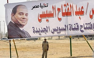 "A policeman stands alert under a billboard with the photo of Egyptian President Abdel-Fattah el-Sissi at the Cairo-Ismailia desert road in Egypt, Thursday, Aug. 6, 2015. Arabic reads, ""long live Egypt, President Abdel-Fattah el-Sissi, opening of the new Suez canal."" (AP Photo/Amr Nabil)"