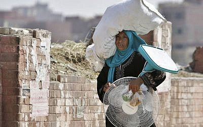An Egyptian farmer carries an electric fan as she walks through a Cairo street , Egypt, Tuesday, Aug. 11, 2015. (AP Photo/Amr Nabil)