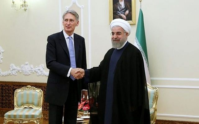 Iran's President Hassan Rouhani, right, welcomes then-British Foreign Secretary Philip Hammond at the start of their meeting in his office, in Tehran, Iran, Monday, Aug. 24, 2015. (AP Photo/Ebrahim Noroozi)