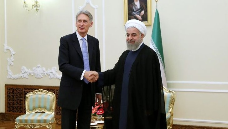 Iran's President Hassan Rouhani, right, welcomes British Foreign Secretary Philip Hammond at the start of their meeting in his office, in Tehran, Iran, Monday, Aug. 24, 2015. (AP Photo/Ebrahim Noroozi)