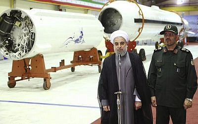 Iran's President Hassan Rouhani, left, briefs the media as Defense Minister Hossein Dehghan listens after unveiling the surface-to-surface Fateh-313, or Conqueror, missile in a ceremony marking Defense Industry Day, Iran, August 22, 2015. (Iranian Presidency Office via AP)