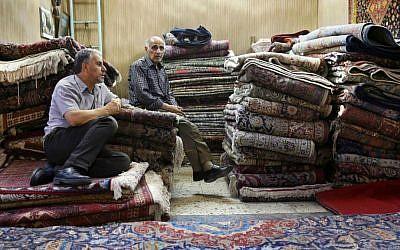 In this Monday, Aug. 10, 2015 photo, Iranian merchants wait for customers at a carpet shop in Tehran's old main bazaar, Iran. (AP Photo/Vahid Salemi)